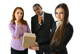 Business woman holding a box in front of her colleagues — Stock Photo