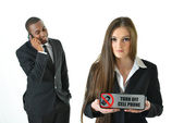 Business woman holding Turn off cell phone sign  with serious expression and a business man speaking on the phone — Stock Photo