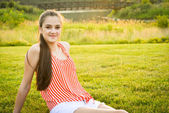 Happy and healthy girl sitting in the park during dusk — Stock Photo