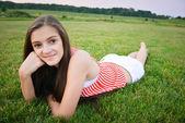 Donna felice con la mano sul mento mentre sdraiato sull'erba — Foto Stock