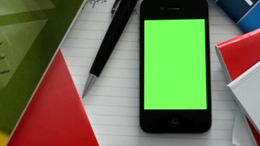 Smartphone (green screen) with workbooks, paper and pen - closeup — Stock Video