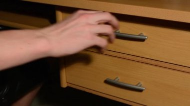 Hand (young man) inserts some papers into the desk drawer — Stock Video