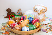 Easter decoration - painted eggs in a basket and a ram to eat — Zdjęcie stockowe