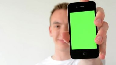Man with a phone (green screen) - man is smiling man shows phone to camera — 图库视频影像