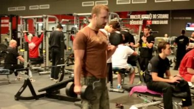 Man strengthens the pectoral muscles in fitness. Workout bench press and biceps — Stock Video
