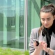Business woman works on mobile and then smiles before bussines building — Stock Video #46452061