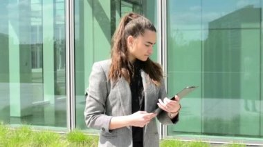 Business woman look to clipboard(paper) before business building — Vídeo de Stock