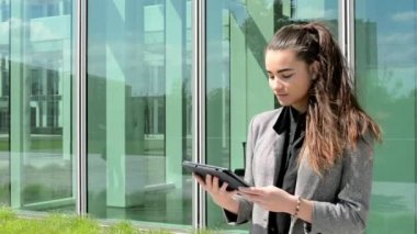 Business woman looks at tablet before business building — Stock Video