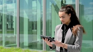Business woman looks at tablet and then smiles before business building — Stock Video