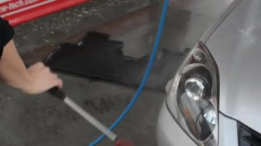 Man washing car with water (spray hose) — Vídeo Stock