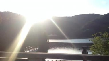 Fast ride over the bridge with sun rays - lake with forest in the background - sunset — Stock Video