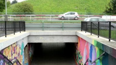 Graffiti on the wall - pedestrian underpass and cars on the road — 图库视频影像