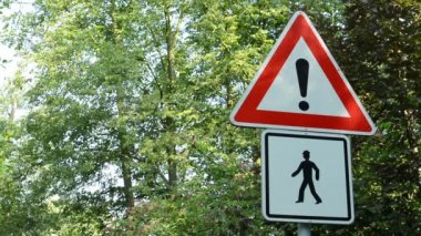 Traffic signs - attention:pedestrian(walkers) - green trees in background — Stock Video