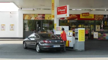 Gas station (oil pump) Shell in the city -with cars and people:worker of station — Stock Video