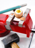 Egg, vise, chisel  and hammer — Stock Photo