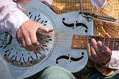 Street musician playing a dobro guitar — Stock Photo