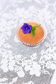 Cupcake on a white lace tablecloth — Stock Photo