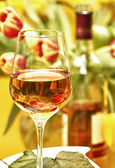 Wine in a glass before tulips and bottle — Stock Photo