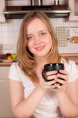 Young happy woman drink morning coffee in kitchen — Stock Photo
