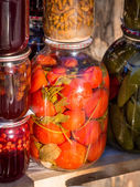 Jars with traditional home-made tomatoes and other preserves — Stock Photo