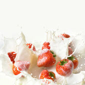 Red strawberry fruits falling into the milk — Stock Photo
