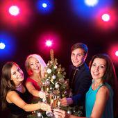 Happy people around the Christmas tree — Stock Photo