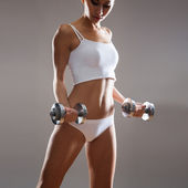 Slim woman with dumbbells. — Stock Photo