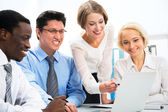 Happy business people gathered around laptop — Stock Photo
