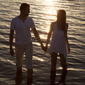 Couple walking by the sea at sunset — Stock Photo