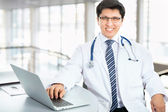 Smiling doctor posing with laptop — ストック写真