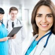 Female doctor standing in front of her team — Stock Photo #44797529