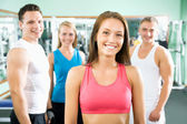 Woman smiling in front of a group of gym people — Stock Photo