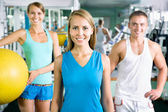 Woman smiling  in front of a group of gym people — Stockfoto