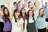 Students with hands raised — Stock Photo