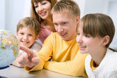 Familia examinando un globo — Foto de Stock