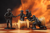 Toy soldiers kill chess King in fire. — Stock Photo