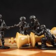 Toy soldiers kill chess King — Stock Photo #44494721