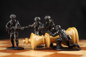 Toy soldiers kill chess King — Stock Photo