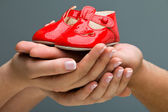 Woman and her husband holding baby shoes in their hands. Mom and Dad Expecting a baby. — Stock Photo