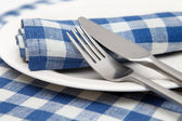 Linen napkins in blue checked with a knife, fork and plate closeup. — Stock Photo