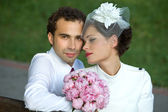 Bride and groom with a bouquet of flowers — Stock Photo