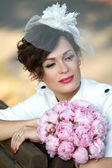 Portrait of an extravagant bride with a bouquet of flowers. — Stock Photo