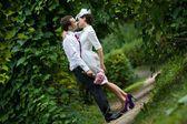 Wedding theme. The groom kisses the bride in a botanical garden. — Stock Photo