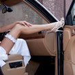 Wedding. Bride's leg in a garter and a shoe on a car's door. Young lady sitting out of the car. — Foto de Stock