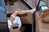 Wedding. Bride's leg in a garter and a shoe on a car's door. Young lady sitting out of the car. — Stok fotoğraf
