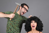 Concept - Idea. Creative team at work. Man is hammering nails into a girl's head. — Stock Photo