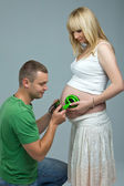 Baby tummy listening to music. Husband put the headphones to pregnant wife's belly, the baby listening to music. — Stock Photo