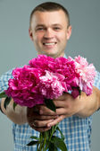 Greetings. Close up of smiling man giving bouquet of flowers. — Stock Photo