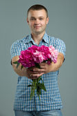 Greetings. Man giving bouquet of flowers. Young beautiful enamored man casual style with flowers. — Stock Photo