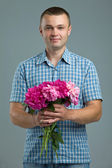 Greetings. Smiling man casual style with flowers. — Stock Photo